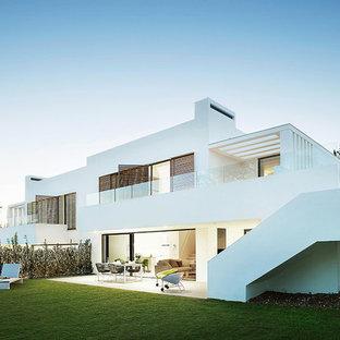 Imagen de fachada blanca, contemporánea, de tamaño medio, de tres plantas, con revestimiento de estuco y tejado plano