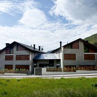 Ejemplo de fachada de casa gris, actual, de dos plantas, con revestimiento de piedra, tejado a dos aguas y tejado de metal