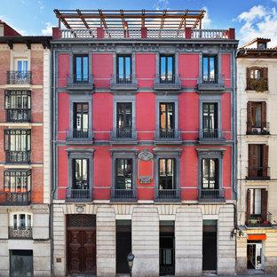 Ejemplo de fachada de piso roja, tradicional, de tres plantas, con tejado plano