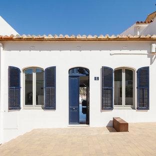 Diseño de fachada de casa blanca, mediterránea, a niveles, con tejado plano y tejado de teja de barro