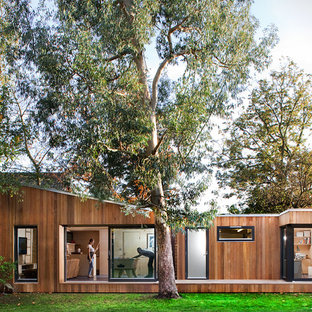 Small and brown contemporary one floor house exterior in Barcelona with wood cladding and a flat roof.
