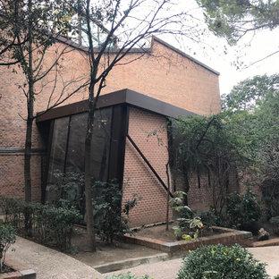 Modelo de fachada marrón, urbana, de tamaño medio, de una planta, con revestimiento de ladrillo, tejado de un solo tendido y tejado de metal