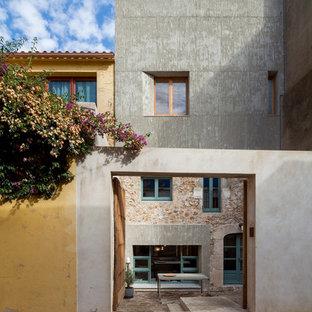 Foto de fachada gris, mediterránea, de tamaño medio, de tres plantas, con revestimientos combinados y tejado plano