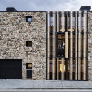 Modelo de fachada de casa pareada marrón, actual, de tamaño medio, de tres plantas, con revestimiento de piedra y tejado plano