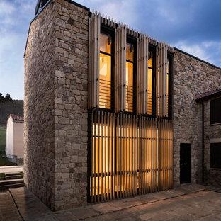 Foto de fachada de casa marrón, contemporánea, de tamaño medio, de tres plantas, con revestimiento de piedra, tejado a dos aguas y tejado de teja de barro