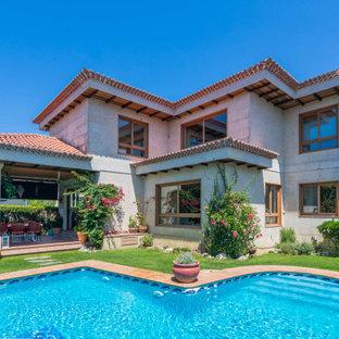 Diseño de fachada de casa gris, mediterránea, de dos plantas, con tejado a cuatro aguas y tejado de teja de barro