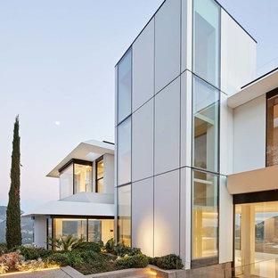 Modelo de fachada de casa blanca, minimalista, grande, de tres plantas, con revestimientos combinados y tejado plano