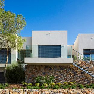 Imagen de fachada de casa blanca, moderna, grande, de dos plantas, con revestimientos combinados y tejado plano
