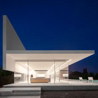 Diseño de fachada de casa blanca, minimalista, de una planta, con revestimiento de vidrio y tejado plano