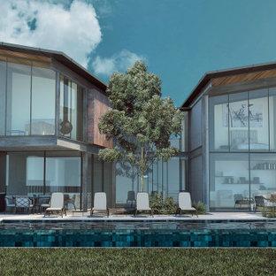 Idées déco pour une grand façade de maison grise moderne à un étage avec un revêtement mixte, un toit papillon et un toit mixte.