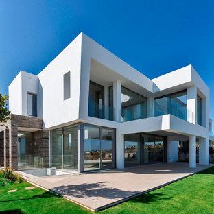 Imagen de fachada de casa blanca, actual, grande, de dos plantas, con tejado plano y revestimientos combinados