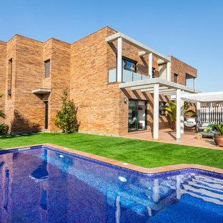 Foto de fachada de casa mediterránea, de dos plantas, con revestimiento de ladrillo y tejado plano
