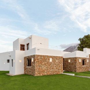 Foto de fachada de casa multicolor, mediterránea, de tamaño medio, de dos plantas, con revestimientos combinados y tejado plano