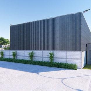 Idee per la facciata di un appartamento ampio grigio industriale a due piani con rivestimento in metallo, tetto a capanna e copertura in metallo o lamiera