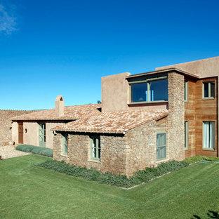 Foto de fachada beige, mediterránea, grande, de dos plantas, con revestimientos combinados y tejado a dos aguas