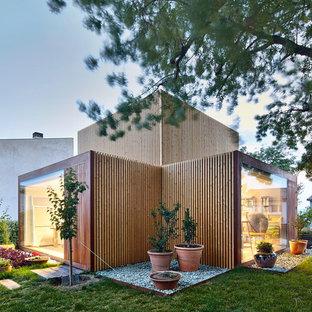 Modelo de fachada de casa marrón, nórdica, de tamaño medio, de dos plantas, con revestimiento de madera y tejado plano