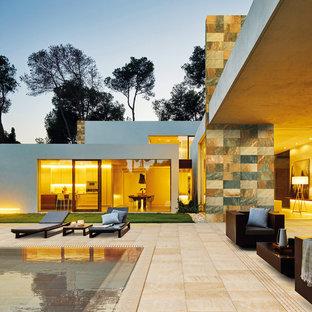 Ispirazione per la facciata di una casa grande beige contemporanea a due piani con rivestimento in pietra e tetto piano