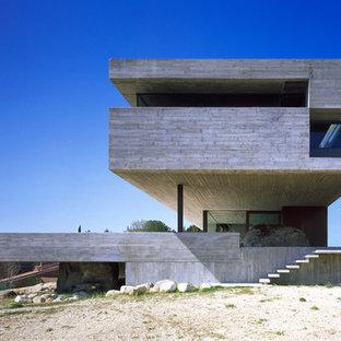 Foto della facciata di una casa ampia grigia moderna a tre piani con rivestimento in cemento e tetto piano