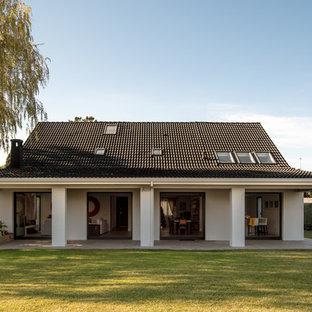 Ejemplo de fachada de casa blanca, contemporánea, grande, de dos plantas, con revestimiento de estuco, tejado a dos aguas y tejado de teja de barro