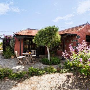 Diseño de fachada roja, mediterránea, pequeña, de una planta, con revestimientos combinados y tejado a dos aguas