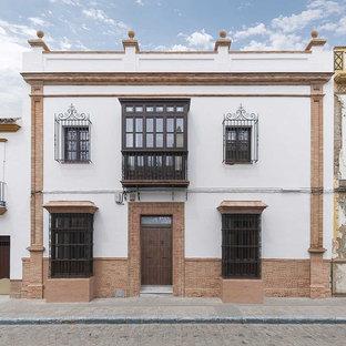 Ejemplo de fachada blanca, clásica renovada, de tamaño medio, de dos plantas, con revestimientos combinados y tejado plano