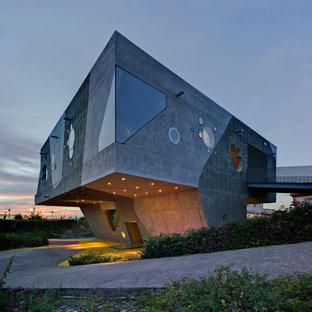 Foto de fachada de casa gris, contemporánea, grande, de dos plantas, con revestimiento de hormigón y tejado plano
