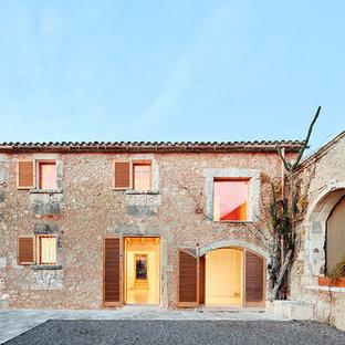 Foto de fachada de casa beige, mediterránea, de dos plantas, con revestimiento de piedra, tejado a dos aguas y tejado de teja de barro