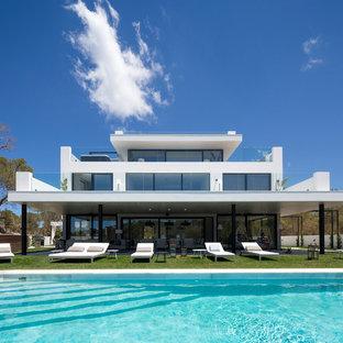 Modelo de fachada de casa blanca, contemporánea, grande, de tres plantas, con tejado plano y revestimiento de estuco