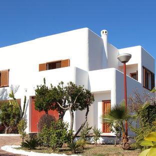Imagen de fachada de casa blanca, mediterránea, de dos plantas, con tejado plano
