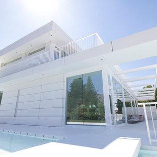 Diseño de fachada blanca, contemporánea, grande, de dos plantas, con revestimientos combinados y tejado plano