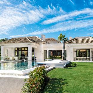 Ejemplo de fachada blanca, mediterránea, de tamaño medio, de una planta, con revestimientos combinados y tejado a cuatro aguas