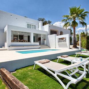 Imagen de fachada blanca, costera, de tamaño medio, de dos plantas, con revestimiento de estuco y tejado plano