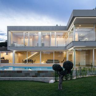 Modelo de fachada de casa gris, contemporánea, grande, de dos plantas, con revestimientos combinados y tejado plano