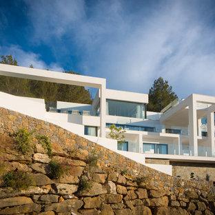 Modelo de fachada blanca, contemporánea, de tres plantas, con revestimiento de estuco y tejado plano