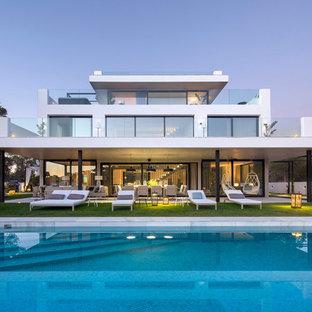 Ejemplo de fachada blanca, contemporánea, grande, de tres plantas, con revestimientos combinados y tejado plano