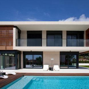 Modelo de fachada blanca, contemporánea, grande, de dos plantas, con revestimientos combinados y tejado plano