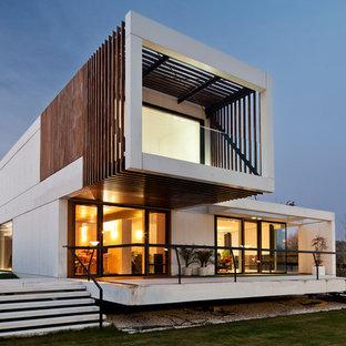 Foto de fachada blanca, contemporánea, de tamaño medio, de dos plantas, con revestimientos combinados y tejado plano