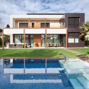 Foto de fachada marrón, actual, de tamaño medio, de dos plantas, con revestimientos combinados y tejado plano