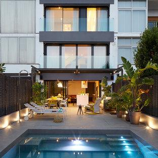 Diseño de fachada blanca, actual, de tamaño medio, de tres plantas, con revestimientos combinados y tejado plano