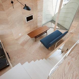 Inredning av ett industriellt litet allrum med öppen planlösning, med ett musikrum, beige väggar, plywoodgolv, en väggmonterad TV och beiget golv