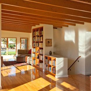 ボストンの中サイズのミッドセンチュリースタイルのおしゃれなオープンリビング (オレンジの床、ライブラリー、白い壁、濃色無垢フローリング、テレビなし) の写真