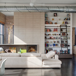 This is an example of a large industrial open concept family room in Chicago with white walls, a library, concrete floors, no fireplace, a built-in media wall and grey floor.