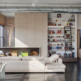 シカゴの大きいインダストリアルスタイルのおしゃれなファミリールーム (白い壁、ライブラリー、コンクリートの床、暖炉なし、埋込式メディアウォール、グレーの床) の写真