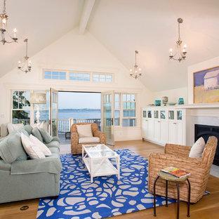 シアトルの大きいビーチスタイルのおしゃれなファミリールーム (白い壁、無垢フローリング、標準型暖炉、石材の暖炉まわり) の写真