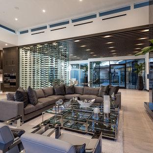ラスベガスの大きいコンテンポラリースタイルのおしゃれなファミリールーム (石材の暖炉まわり、壁掛け型テレビ、ベージュの床、ホームバー、白い壁、淡色無垢フローリング、横長型暖炉) の写真