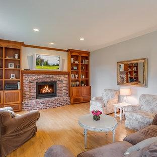 シアトルの大きいエクレクティックスタイルのおしゃれな独立型ファミリールーム (ライブラリー、青い壁、淡色無垢フローリング、標準型暖炉、レンガの暖炉まわり、壁掛け型テレビ) の写真
