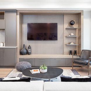 バンクーバーの小さいコンテンポラリースタイルのおしゃれなオープンリビング (グレーの壁、無垢フローリング、壁掛け型テレビ、茶色い床) の写真