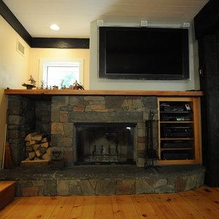 Diseño de sala de estar abierta, campestre, con suelo de madera clara, marco de chimenea de piedra y televisor colgado en la pared