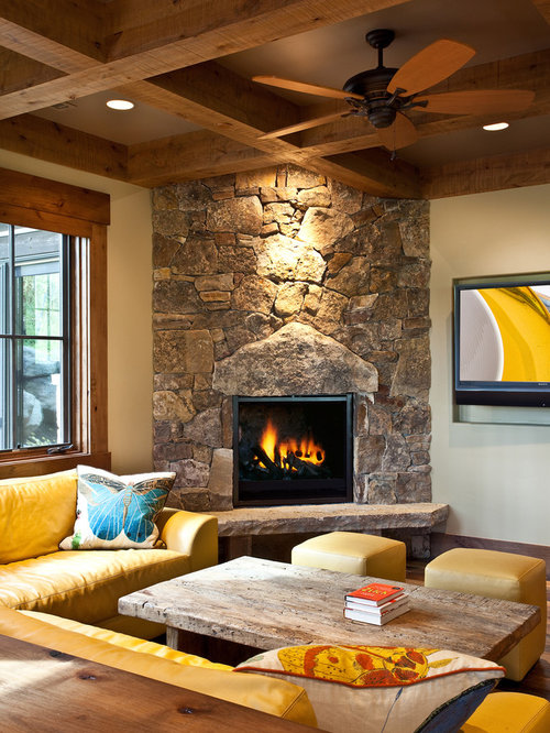 rustic family room idea in other with a corner fireplace