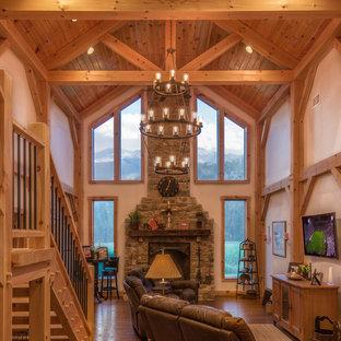 他の地域の広いラスティックスタイルのおしゃれなオープンリビング (白い壁、無垢フローリング、薪ストーブ、石材の暖炉まわり、壁掛け型テレビ、茶色い床) の写真